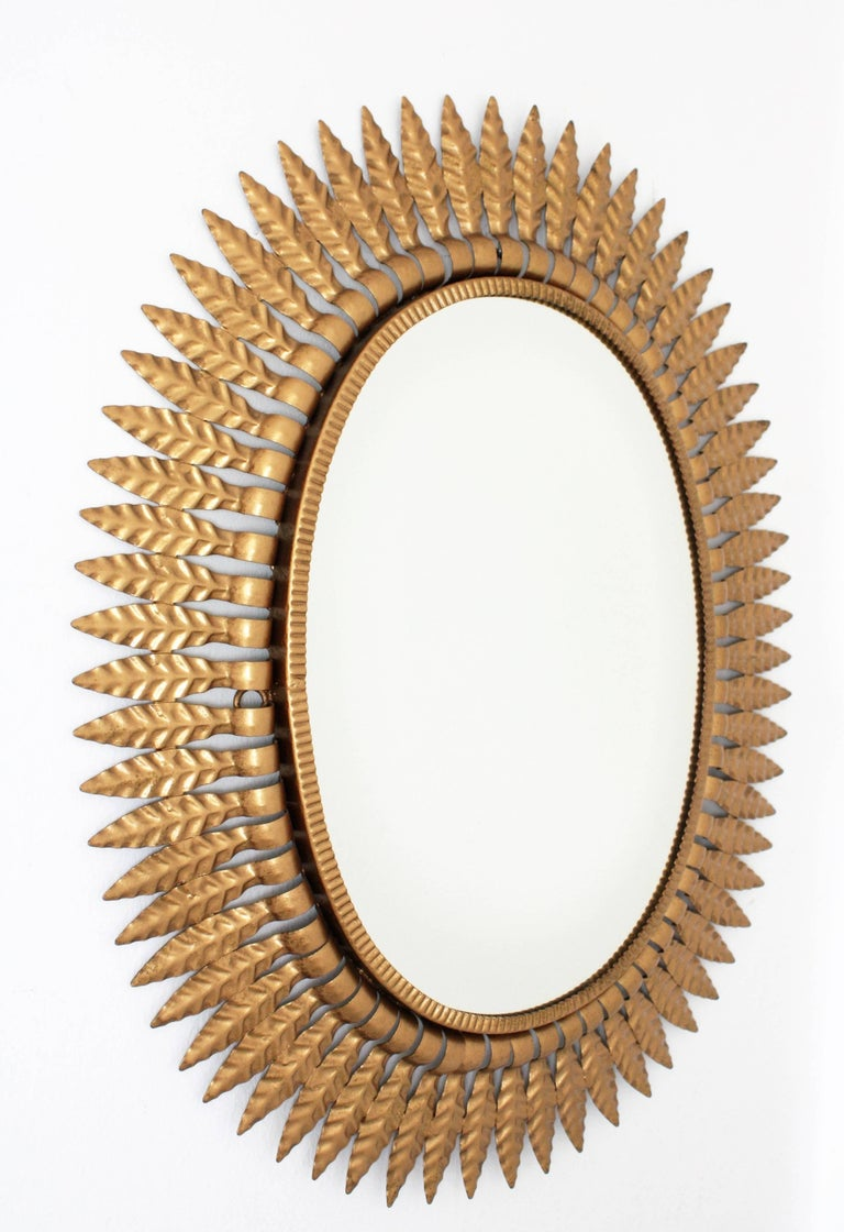 An oval sunburst mirror framed with gilt metal leaves. A highly decorative piece to place alone or creating a wall decoration with other mirrors in this manner. It can be placed in two positions. Spain, 1950s.
