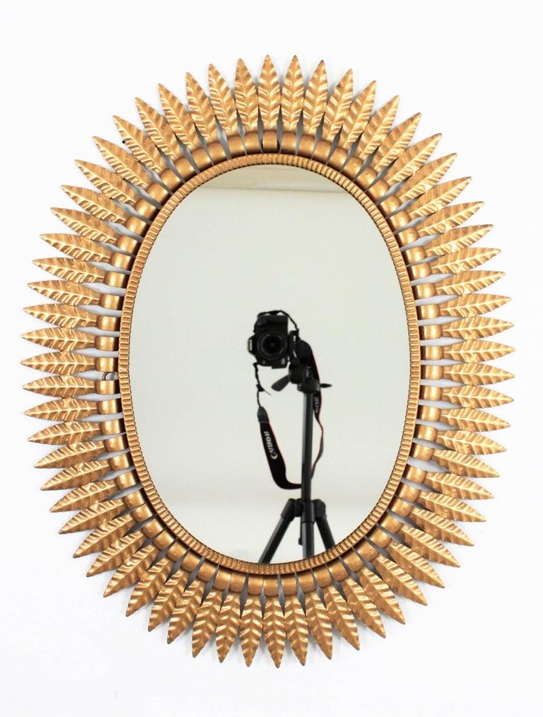 Gilt Spanish Mid-Century Modern Gilded Metal Oval Sunburst Mirror For Sale