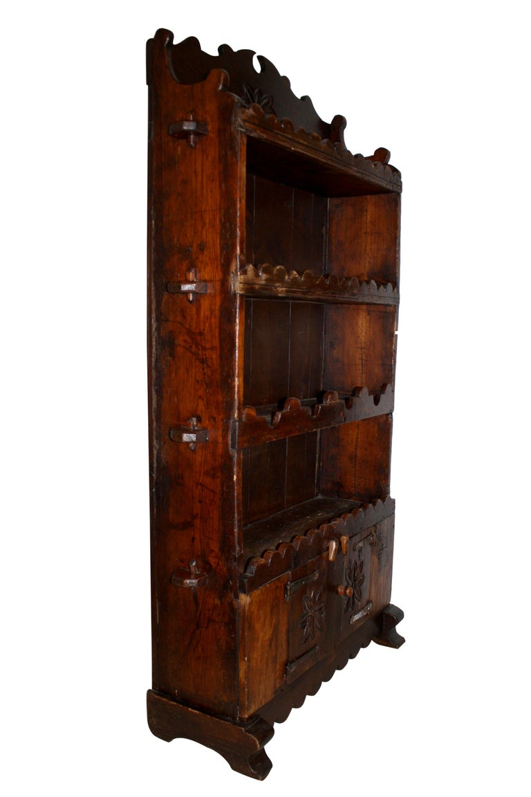 Comprised of four shelves with decorative trim and tusk tenon joinery, a two-door cabinet with long iron hinges, a broken pediment, and hand carved flowers, this oak bookcase brings a rustic, Old World charm to any room. The top three shelves have