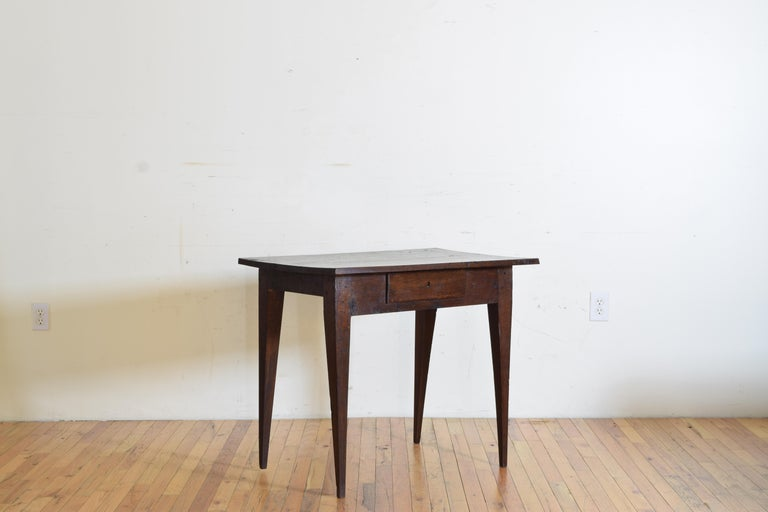 From Pamplona Spain this table has had a large life with a number of cuts and marks to the top, likely a work or kitchen table, the rectangular top above a case housing one-drawer, raised on square tapering legs.