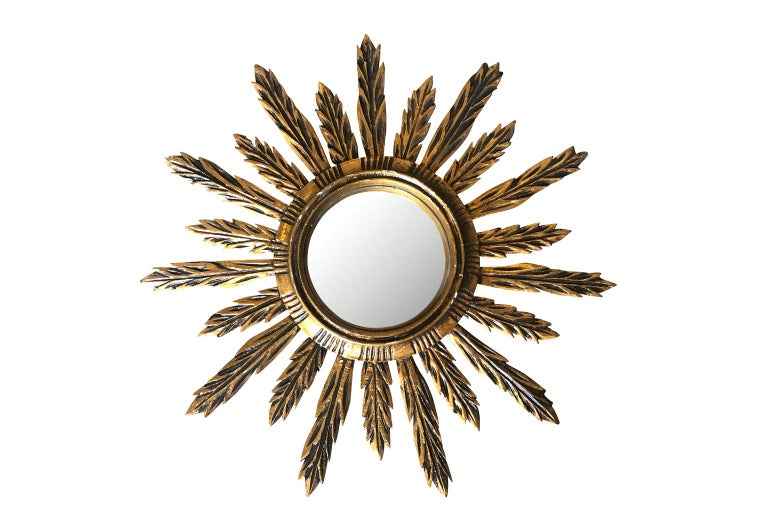 A very lovely Spanish sunburst mirror in hand carved giltwood with its convex mirror. A charming accent piece.