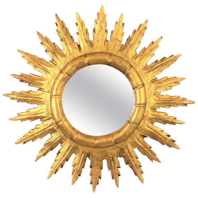 Gold leaf giltwood sunburst mirror in Baroque style. Spain, 1950s. Eye-catching hand carved wood sunburst mirror covered with gesso and gold leaf finishing. A lovely mirror to be placed alone or as a part of a wall composition with more mirrors in