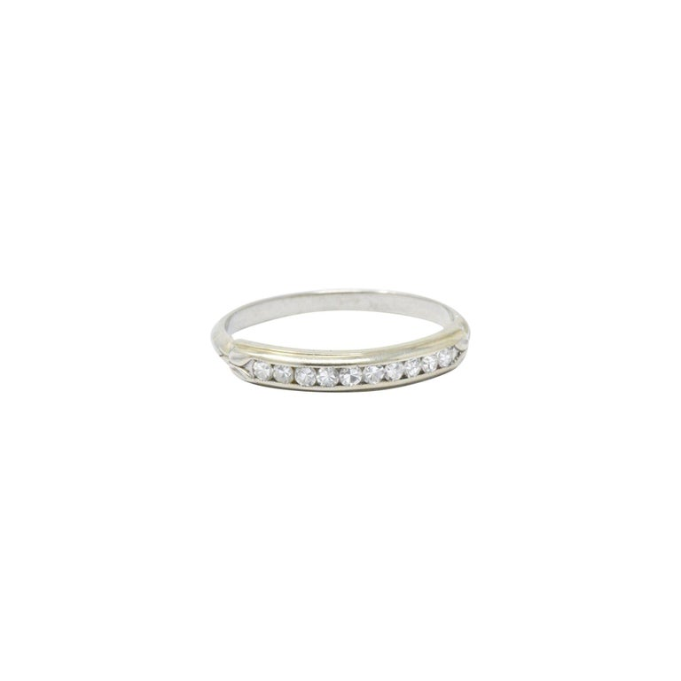 Channel set to the front with ten single cut diamonds, approximately 0.20 carats total, F/G color, VS to SI clarity   Delicate foliate motif detail to the gold flanking the diamonds  Can be worn as a wedding band or as a great stacking ring  Ring