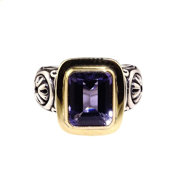 Stunning Sterling Silver ring showcasing an emerald cut blue Iolite bezel set in 18K yellow gold. This is Steven Battelle ring featuring all of his attention to detail and comfort.  The Sterling Silver shank and head are etched and beautifully
