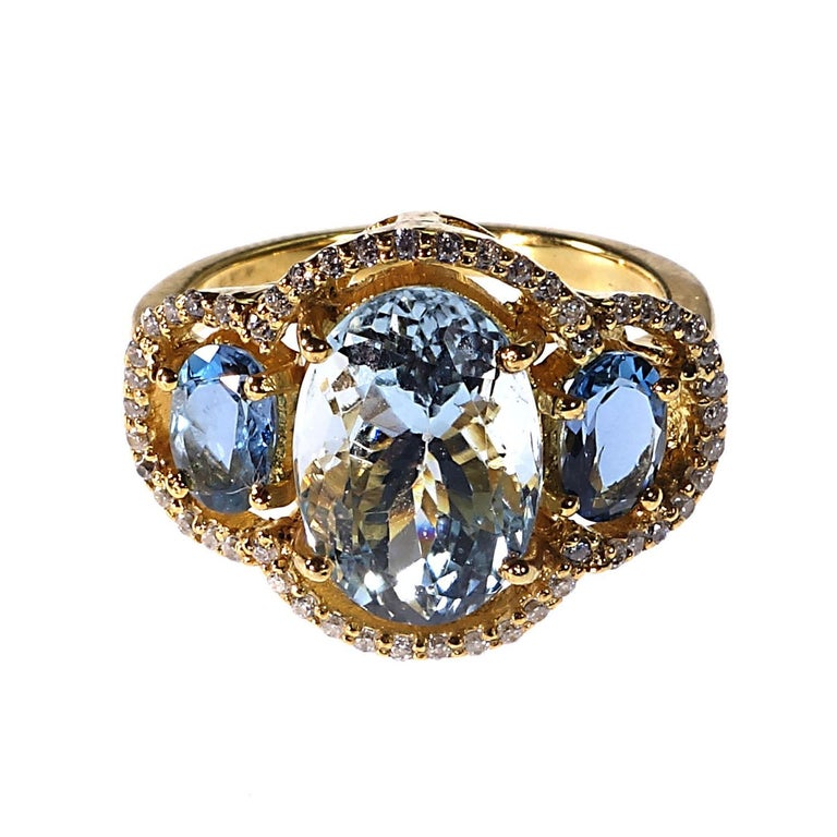 Custom made, glittering ring of oval Aquamarines Halo set with Zircons in glowing 14K yellow gold rhodium on Sterling Silver. One sparkling oval Aquamarine in flanked by two slightly darker oval Aquamarines. All three are surrounded by glittering
