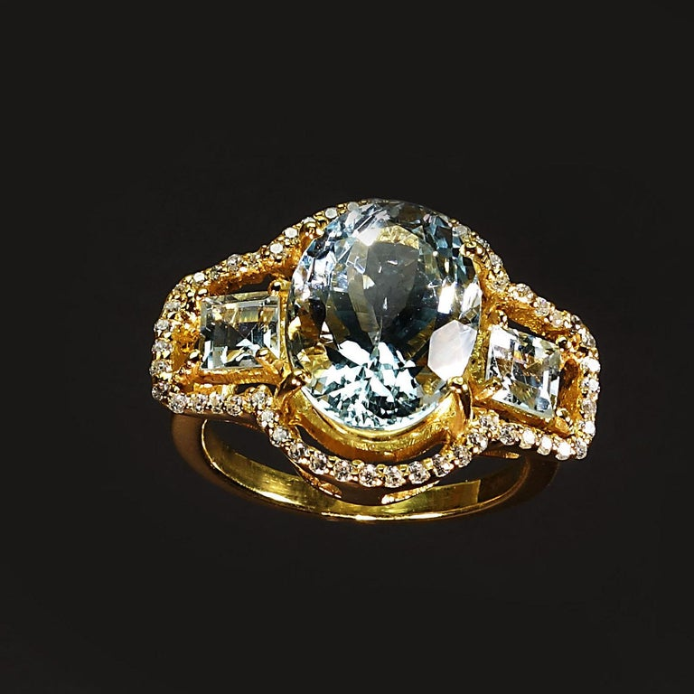 Custom made Cocktail ring of sparkling oval Aquamarine with square Aquamarine side stones. The three Aquamarines are surrounded with glittering Cambodian Zircons.  All of this is set in 14K yellow gold rhodium over Sterling Silver.  This delicious
