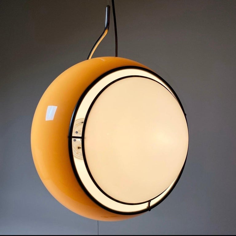 """Model number 4514 the biggest and most beautiful caramel colored """"eye"""" by Harvey Guzzini, Italy, 1974.  The XL sized caramel colored plastic shade hangs tilted on a curved chrome rod and everything is kept in place by the chrome counter weight."""