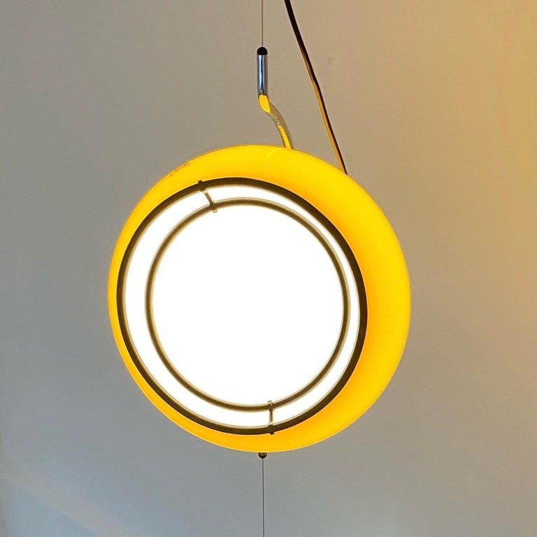 Stunning and awesome are probably the first words which describes this floating light produced by Harvey Guzzini in the early 1970s.   The iconic Art 4513 with the sideway tilted huge yellow shade floating on an almost invisible metal cable. To