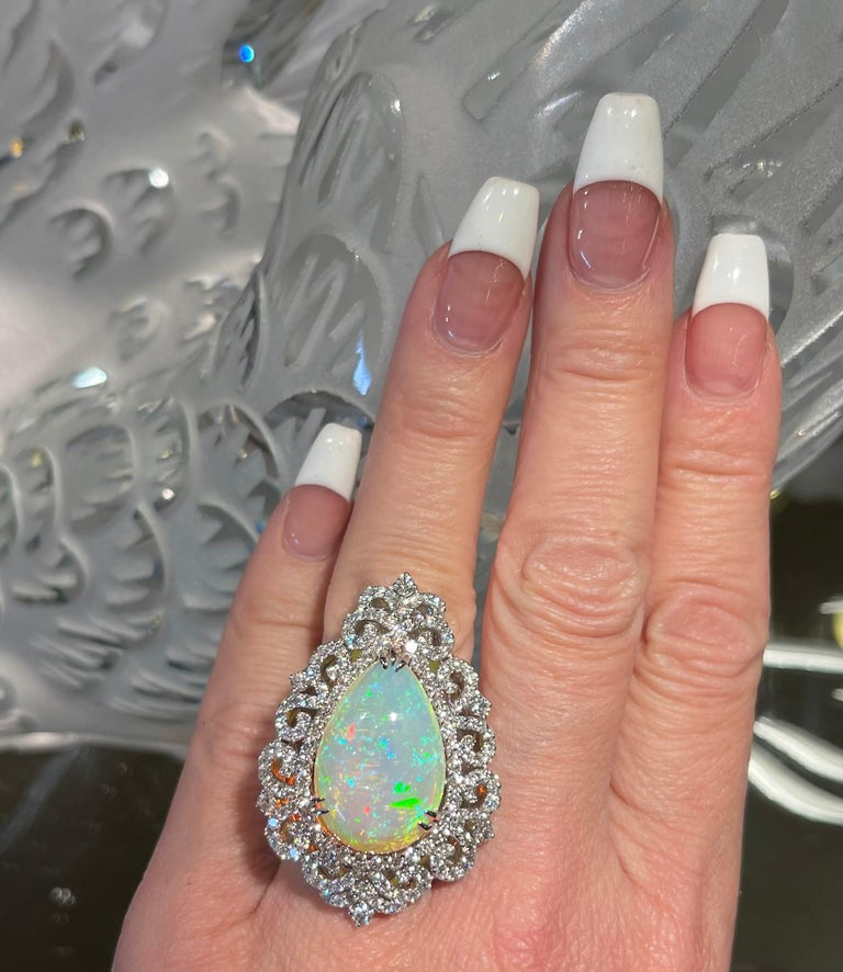 Very showy and totally dazzling, 18 karat white gold natural opal and diamond estate cocktail ring features a 13.62 carat fiery pear shaped opal in the center, surrounded by a halo of sparkling round brilliant diamonds that are further surrounded by
