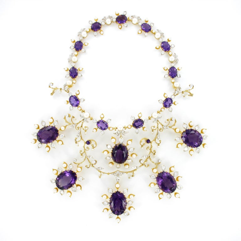 What a show! Spectacular amethyst, diamond and pearl suite consisting of necklace, ear hangers, ring, bangle and brooch. Flowery design in 18 Karat yellow and white gold.  Prong set with a total of 26 oval and round shaped amethysts totaling an