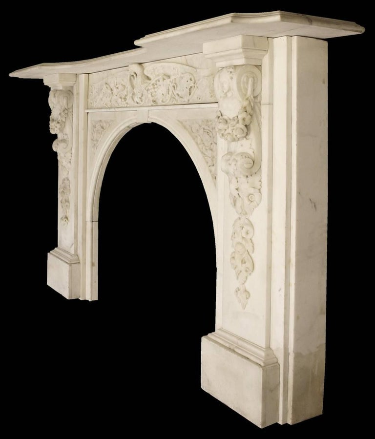 A spectacular large antique early Victorian chimneypiece in ivory white statuary marble. The intricately carved frieze in high relief shows a long grape vine in fruit being held by a spread eagle, which sits above equally well carved spandrels, and