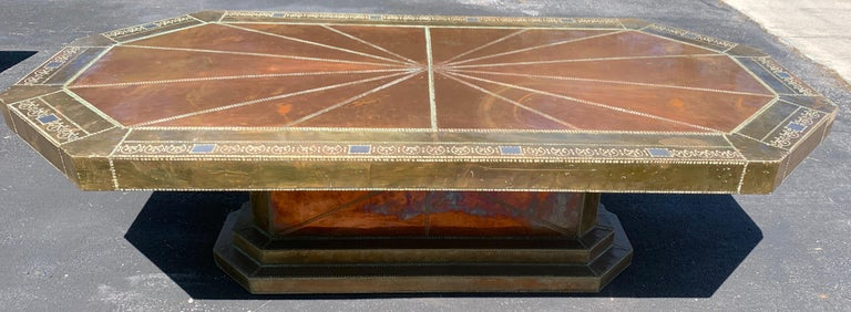 Spectacular copper and brass dining table by Rodolfo Dubarry for King Hassan II, King of Morocco (1961-1999) in two parts, the top beautifully hand tooled in mixed metal, signed in script. Raised on a conforming riveted base. A difficult piece to
