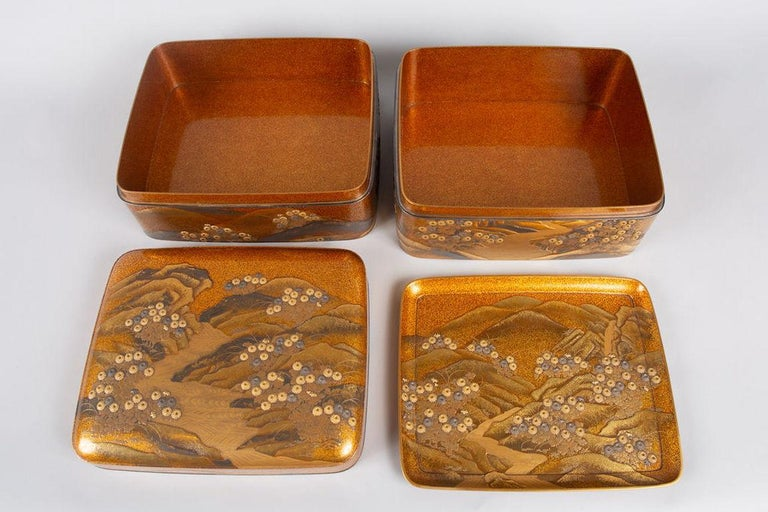 Incense box in nashiji lacquer with design of river flowing through highly defined hills that are strewn with chrysanthemums. Several uses of gold lacquer, cut gold and gold sheeting, along with silver, create a dramatic design of exemplary 19th