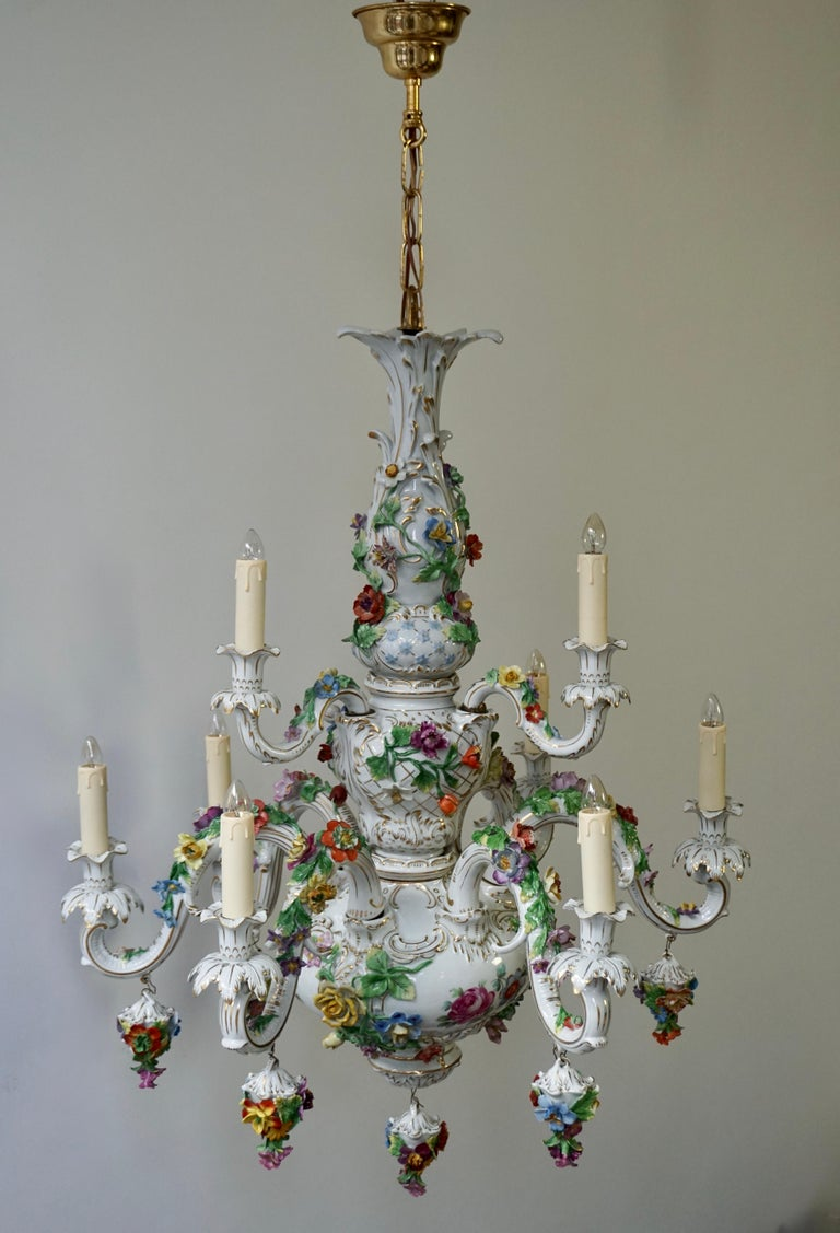 Blanketed in a multitude of floral bouquets, this monumental porcelain chandelier was possible crafted in Italy or Germany. A marvellous example of exceptional artistry, this enchanting tole multi light double tier 9-light fixture exemplifies the