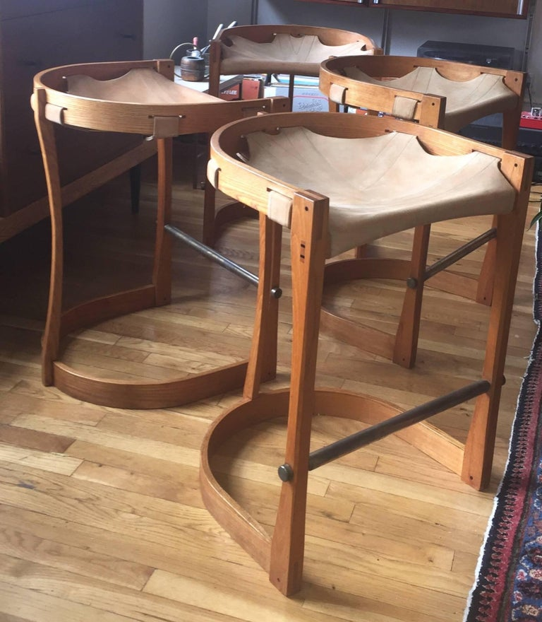 c. 1970 solid bentwood Ash stools with stitched saddle leather sling seats.  Remarkable build quality and subtle details, such as peg and dovetail construction with exposed ebony wood pegging, solid brass foot rests, and intricate  wood carving. The
