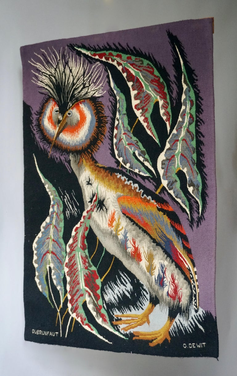 Rare and colorful tapestry of an ornamental crowned crane bird with black and purple background. Signed by renown Belgian artist Edmont Dubrunfaut, circa 1950.