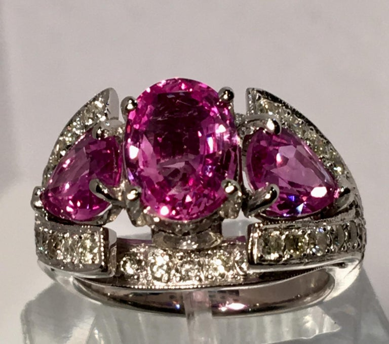 Fantastic from all angles, this custom made, substantial platinum estate three stone ring or engagement ring features a prong set oval cut pink sapphire, flanked with two prong set, pear cut pink sapphire stones, with two bezel set round brilliant