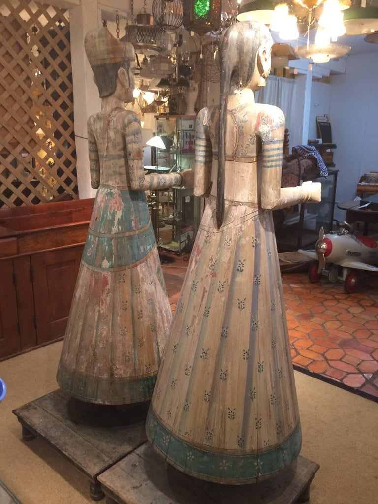 Two extremely large gorgeous vintage Rajasthani figures that may be god and goddess, all hand carved and painted in beautiful naturally distressed condition, having lovely gestural hands, a soft pastel color palette, and original wooden stands. Man