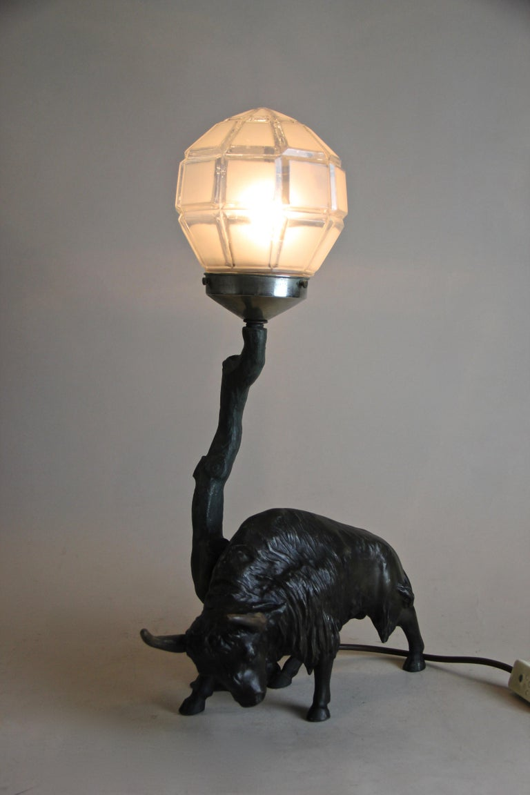 Extraordinary Spelter table lamp from the very early 20th century out of Austria. Depicting a majestic North American bison, this unique table lamp consists of a beautiful designed glass ball which sits on top of a narrow tree trunk, spreading a