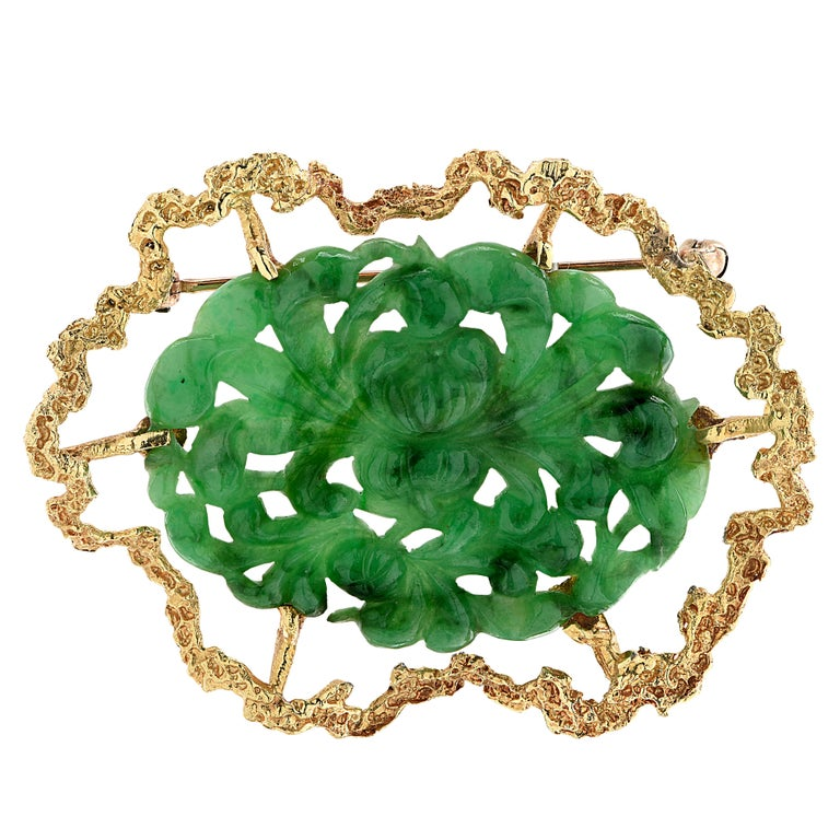 Spectacular brooch pin crafted in yellow gold showcasing a jade carving. The brooch pin measures 1.5 inches in length and 1.9 inches in width. It weighs 10.8 grams.  Our pieces are all accompanied by an appraisal performed by one of our in-house GIA