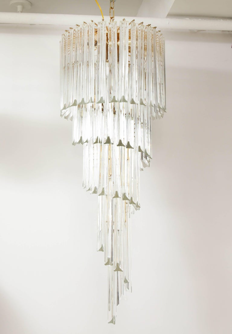 Spiral chandelier with Venini Triedi crystals by Camer. The polished brass frame supports the crystals in a spiral formation and is beautiful when illuminated. The fixture has been newly rewired for the US and comes complete with matching ceiling