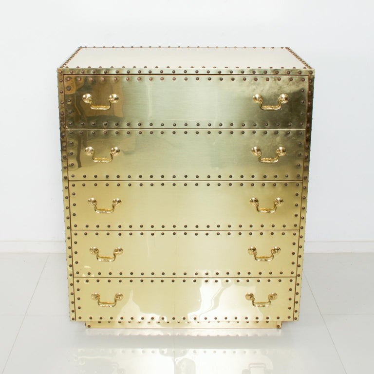 For your pleasure: Fabulous Hollywood regency modern vintage brass studded highboy dresser chest by Sarreid Ltd of Spain, 1970s. Dimensions: 40.5 H x 20.25 D x 34 .25 W Original unrestored condition: stains, scratches, dings and scuffs present.