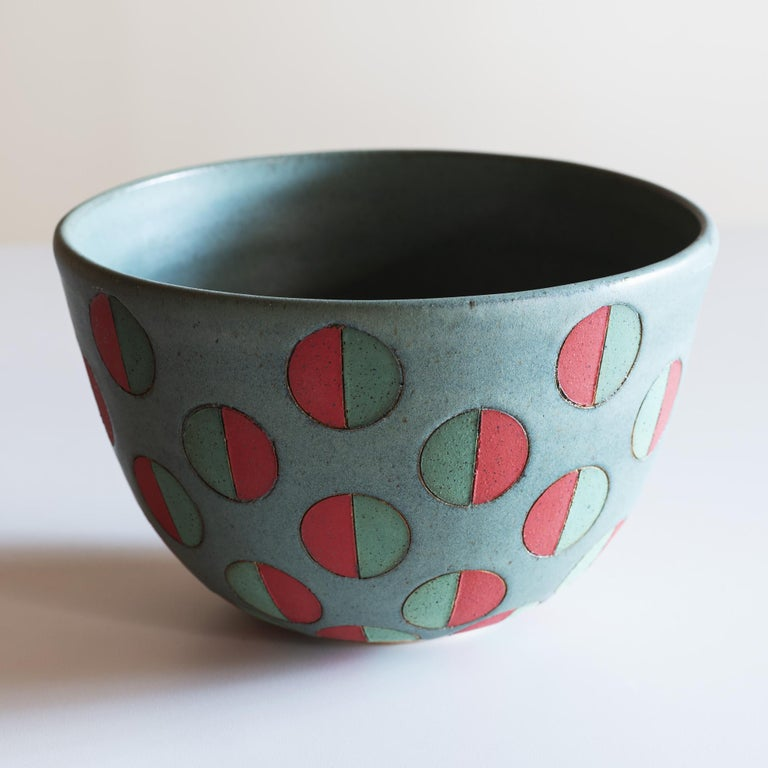 Handsome, large stoneware vessel with split polka dots in green and red.
