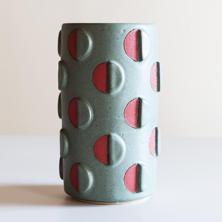 Stoneware vessel with split polka dots in green relief and red.