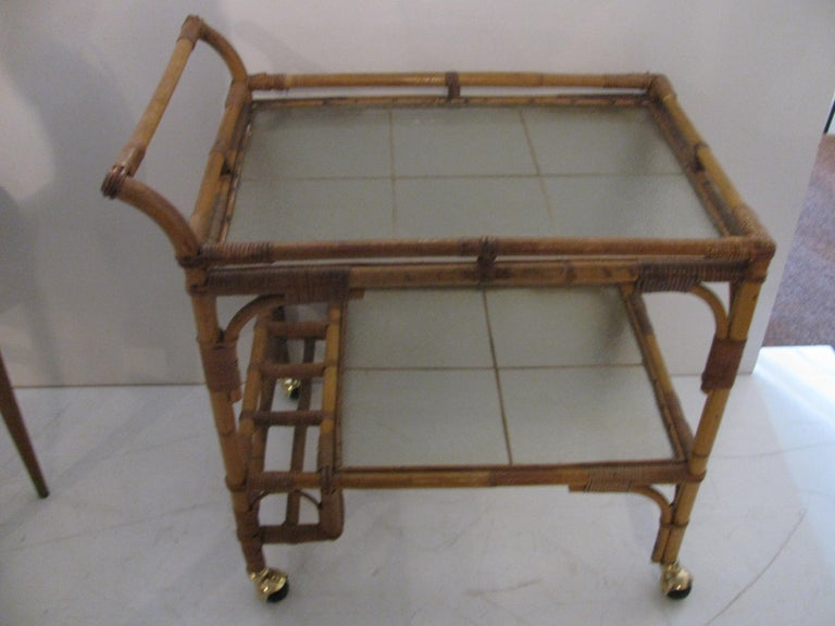 Rattan bar cart with frosted glass shelves. Bottle holder at the base on lower shelf. Measures: Shelf is 17 x 23.5in.