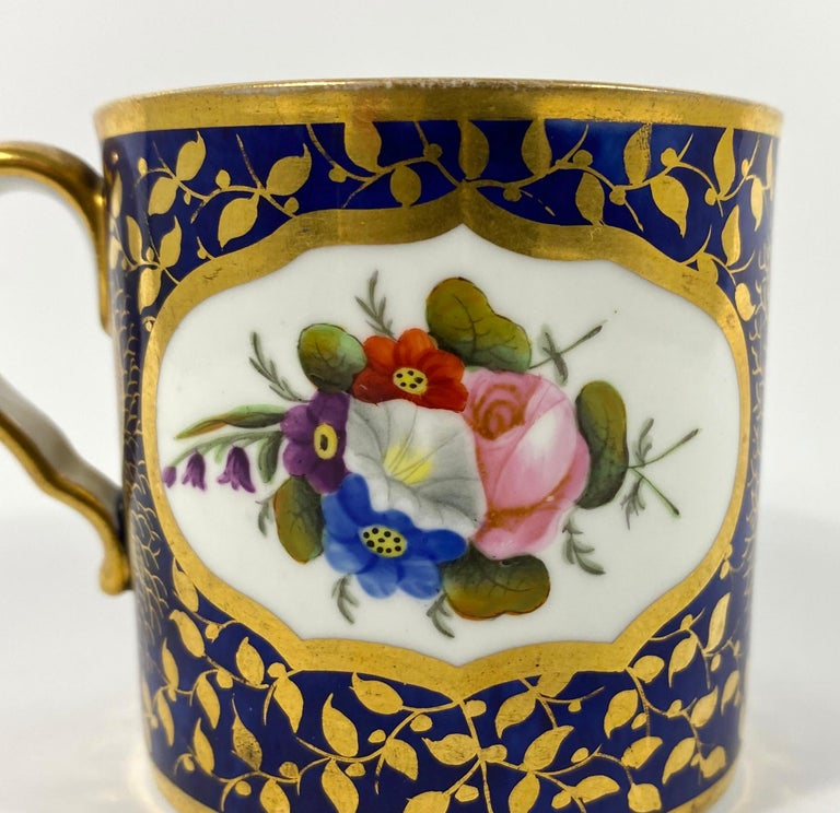 Spode porcelain coffee can, circa 1815. Painted to either side with sprays of flowers, in shaped gilt lined panels. Upon a cobalt blue ground, beautifully gilded with shells, amongst scrolling leaves.