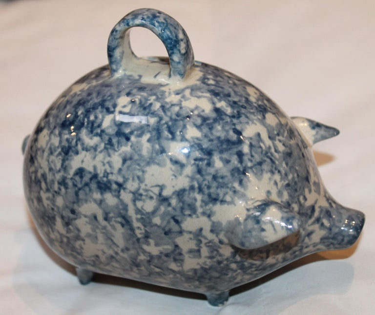 This vintage sponge ware pottery pig bank sits on four legs and has a cork in the bottom of the bank. The condition is very good with a couple age chips on one foot.