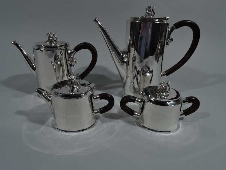Modern sterling silver coffee and tea set. Made by Spratling in Taxco. Each: Ovoid body and stained-wood scroll handle and flat cover with tooled finial in form of seated jaguar– an exotic touch to a spare form. A smart design by the famed Mexican