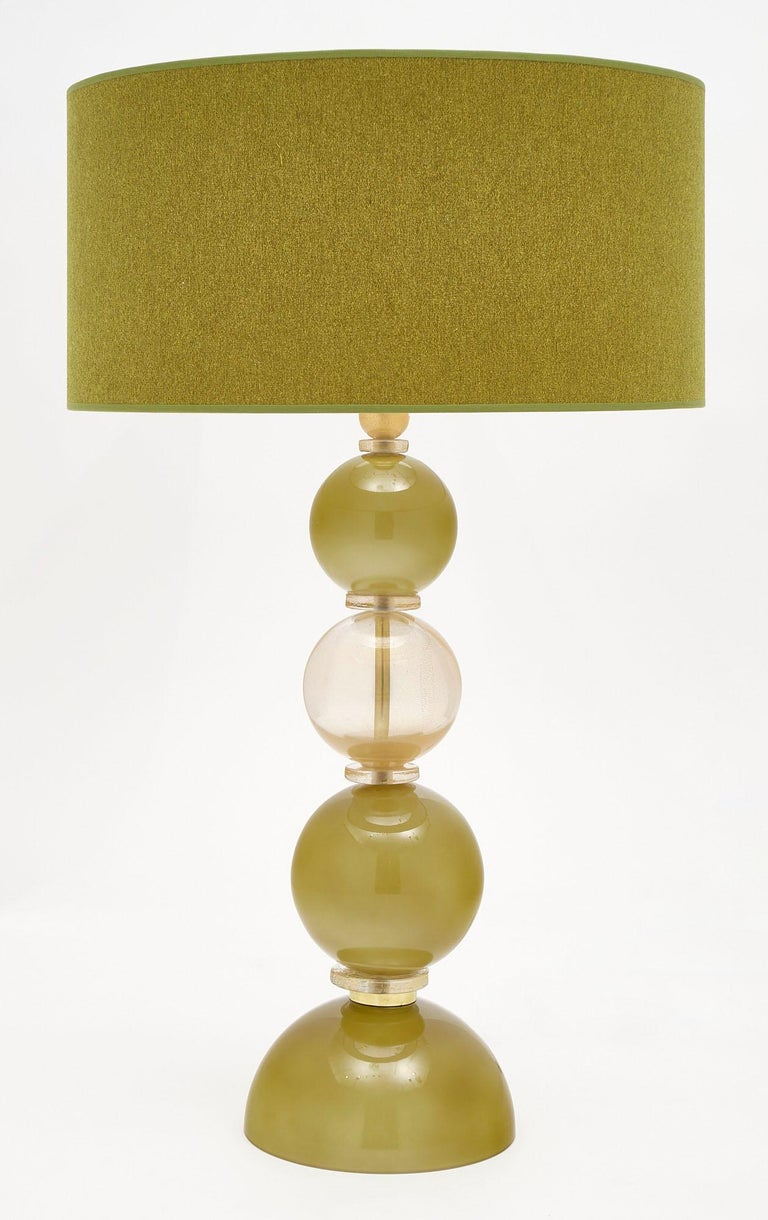 Pair of spring green Murano glass lamps featuring hand-blown glass spheres in spring green and light gold. We love the green linen shades and strong impression of this pair. They have been newly wired to fit US standards.