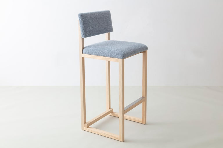 Shown in solid ash, bouclé wool, and brushed stainless steel hardware.   Available with: Wood in ash, cherry, maple, walnut, or white oak  Upholstery in customer's own material or leather (COM+COL)   Metal in brushed brass, antique brass, oil