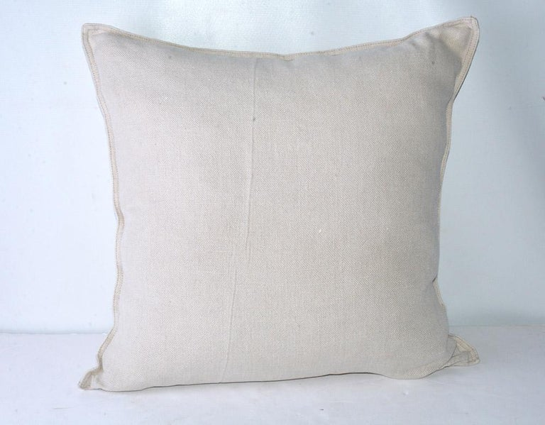 The square beige linen pillow is decorated with a series of printed French words and names. Top: