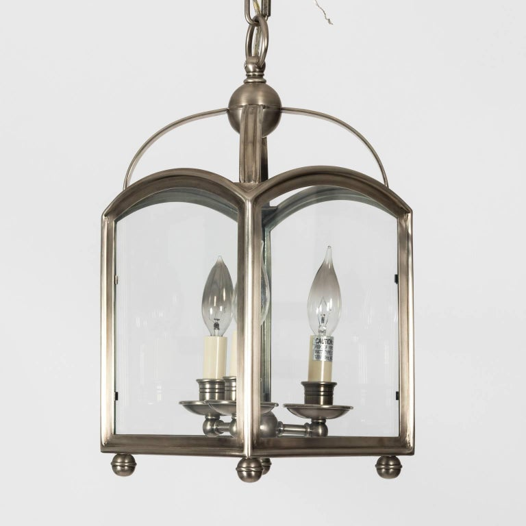 Contemporary square four-pane metal exterior lantern with three lights in a brushed metal finish.