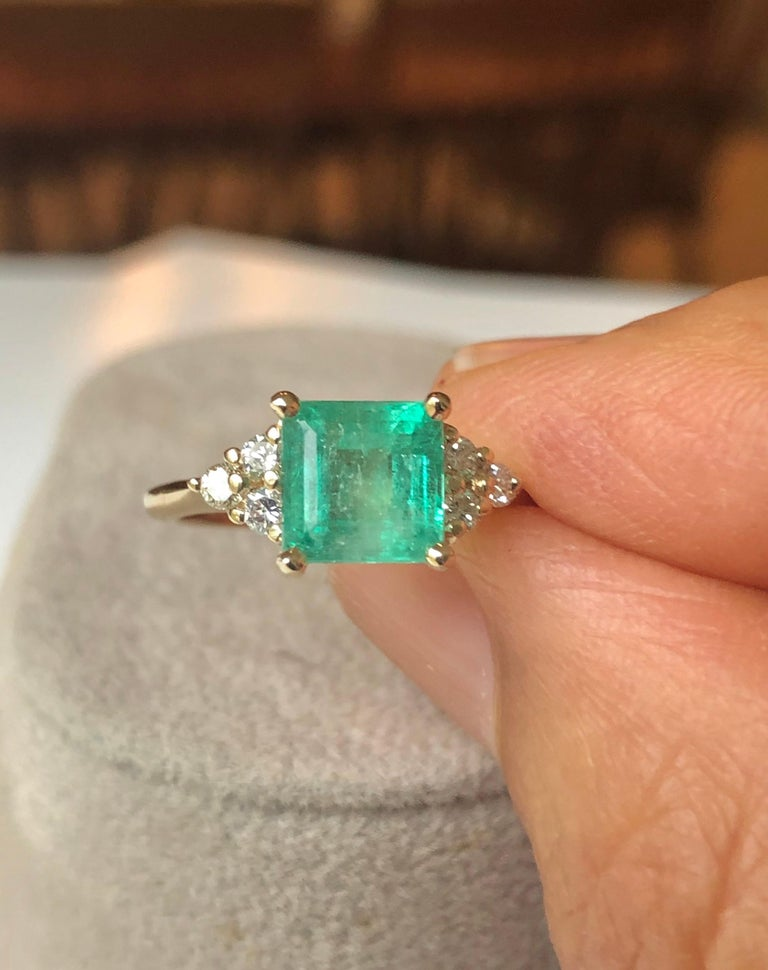 This is a Gorgeous Colombian Emerald and Diamond Engagement Ring set with a square cut emerald weighing 1.70 carats (7.1x7.2mm), within six round brilliant cut diamonds H/SI1 weighing approximately  .30 carats. Set in yellow gold 14K.  Feature one
