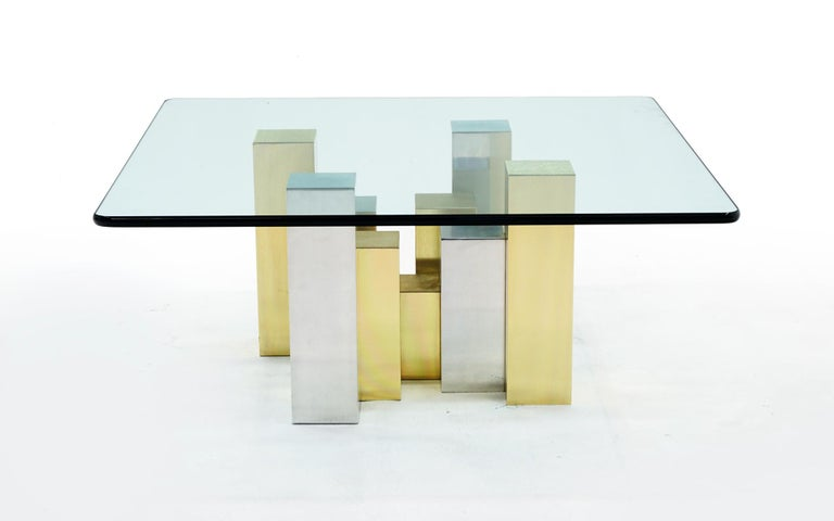 Coffee table in the style of Paul Evans with a glass top and cityscape style base in brushed chrome and brushed brass.
