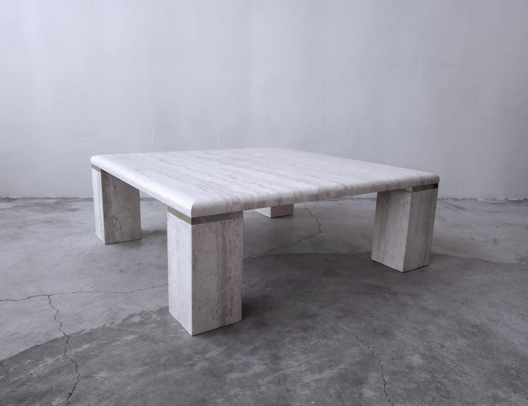 Very elegant, vintage square travertine coffee table. Simple, beautiful piece. Tabletop is a square with 4 large square legs that are manufactured with a nice brass separation detail, classing it up a bit more.   Table is in excellent condition.