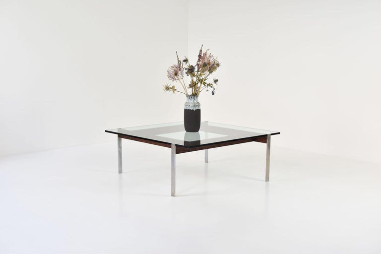 Elegant square Modernist coffee table by (for now) unknown designer or manufacturer. The polished steel frame is partially veneered with rosewood, giving the table an extra touch. The removable glass table top is renewed. Four base elements are
