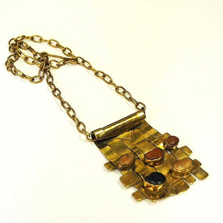 A square, solid and wonderful nature stone necklace with integrated colored stones from the Norwegian fauna. Lovely Scandinavian Modern design by Norwegian silversmith Anna Greta Eker. Norway, 1960s. The necklace has beads of brass layers then