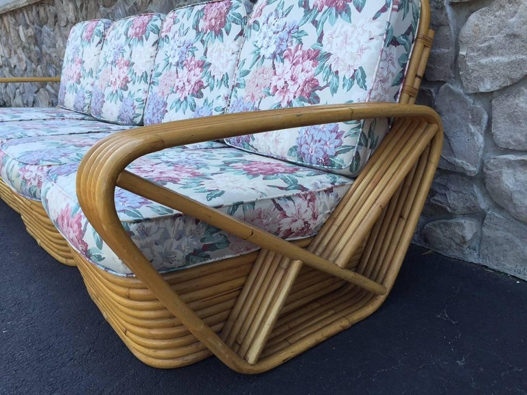 Square pretzel rattan sofa style of Paul Frankl. The sofa has a stacked rattan base and the sofa is in four sectional seating. Original cushions. Measures: 99 W x 37.5 D x 31 H (to top of back cushion).