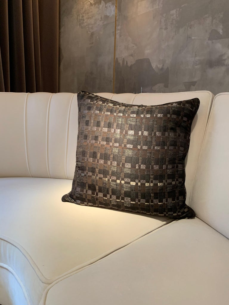 A simple square throw pillow covered in Dedar Reversi fabric.