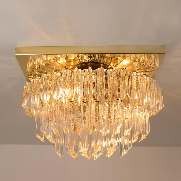 This stylish three-tiered faceted Murano flush mount with 58 clear crystal glass prisms was designed and produced by Venini in Italy from the 1970s. The Venin Murano prisms are suspended on a square gold plated frame. The prisms sparkle with the