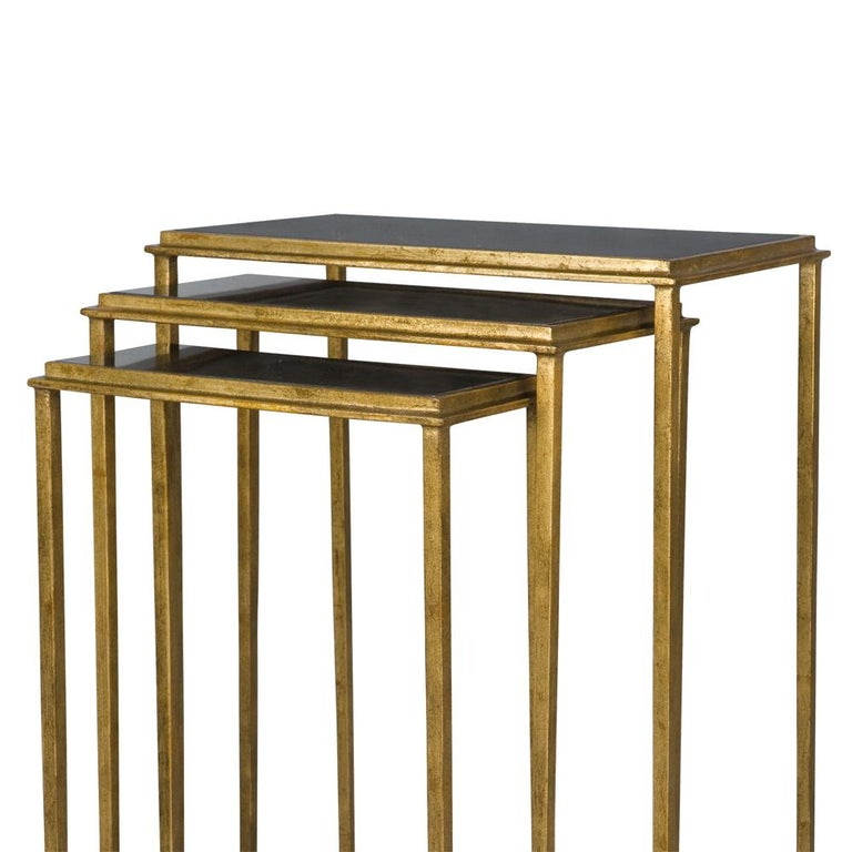A timeless nest of three gilt metal tables, complemented with a black granite inlay Gold iron finish with Italian black granite top Supplied as a set of three.