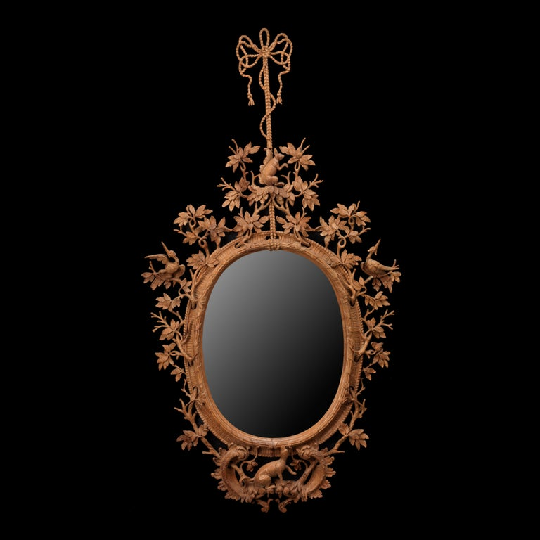 A fine naturalistically carved oval mirror with bird, branch and stylized animal decoration in the manner of Thomas Johnson. An exceptionally fine mirror carved in period old pine with an 18th century wax finish.