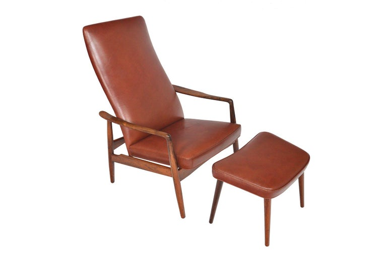 This Danish modern sienna brown leather reclining lounge chair and matching ottoman were designed by Søren Ladefoged for Søren Ladefoged and Søn as Model 72 in 1966. Beautifully crafted with solid Brazilian rosewood spindle legs, this set offers