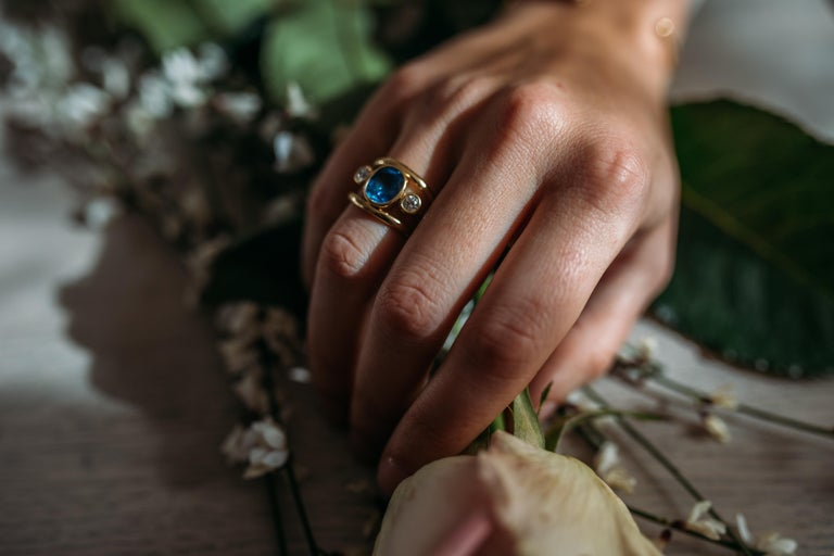 A sophisticated and elegant cocktail ring a beautiful and vibrant corn flower blue, Sri Lankan Sapphire set with a Diamond on each side and set in 18kt yellow gold.  A statement ring that is very comfortable to wear as not set too high and has rub