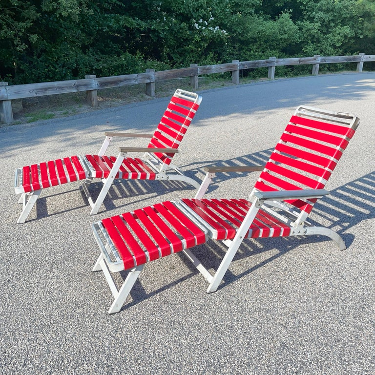 These two folding aluminum lounge chairs were made for the SS United States ocean liner and produced by the Troy Sunshade Company in 1952.  Note the slot for name tag for passengers who would have reserved the chair aboard the ship. Red