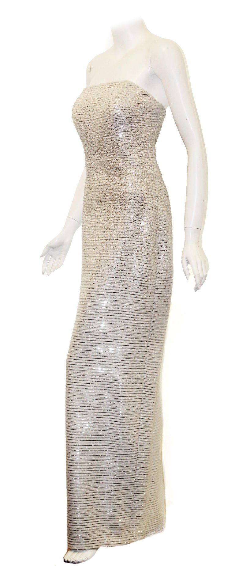 St. John white lattice knit gown interlaced with mini silver sequins and crystals throughout the dress creates a sparkling, signature sophisticated piece.  This strapless gown contains an attached internal bustier for added support.   Gown contains